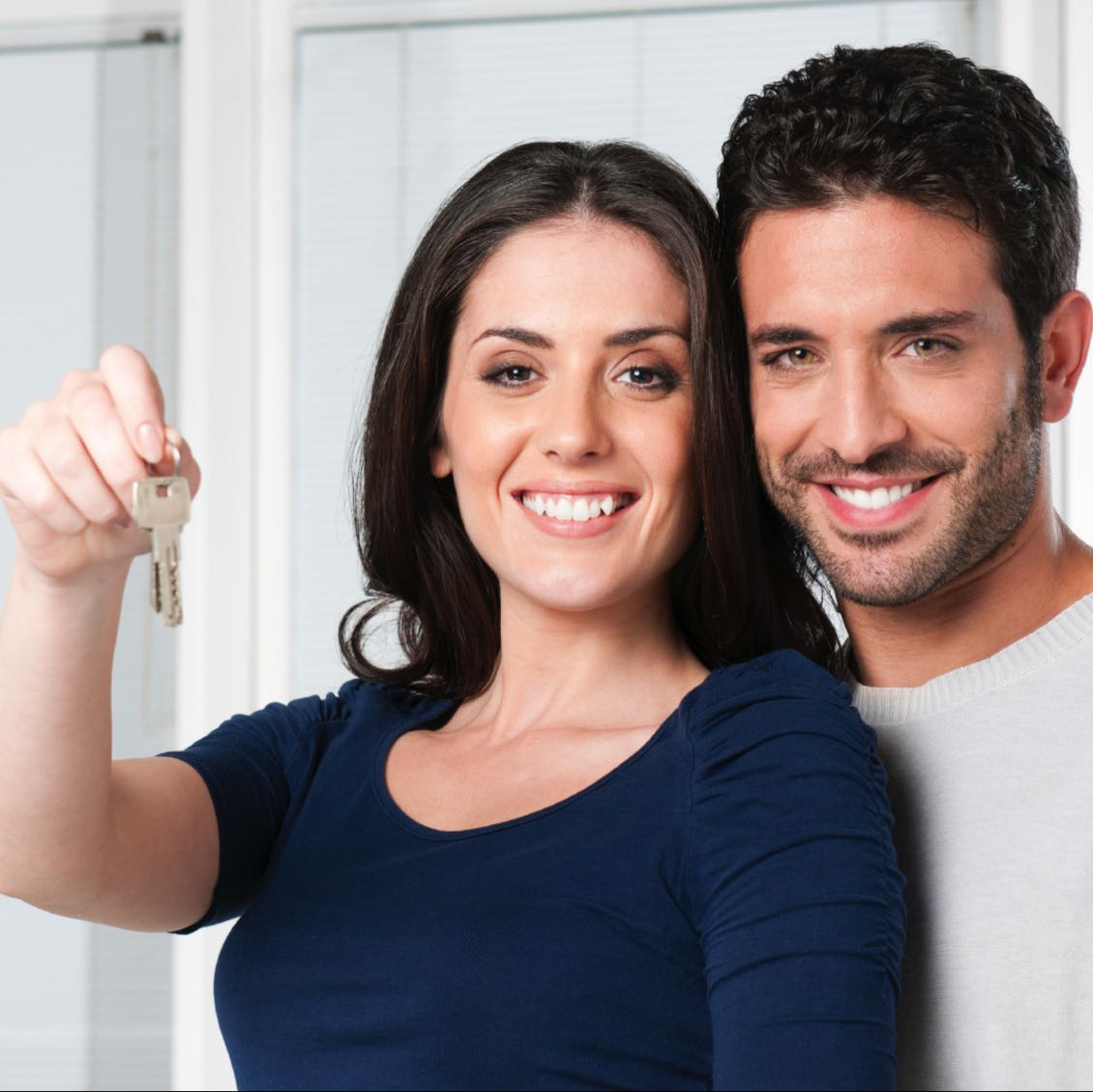 Couple holding keys to new home - residential real estate law at Kelly Santini LLP