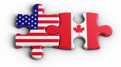 Two puzzle pieces with Canada and USA flag on a piece