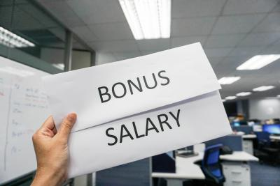 Hand holding two envelopes - one says 'bonus' the other says 'salary'