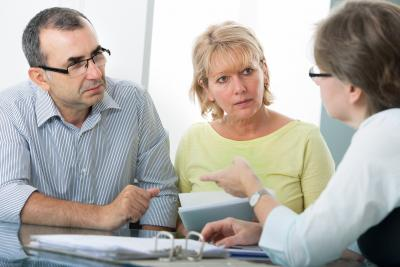 Couple in 60s at table receiving advice from another person