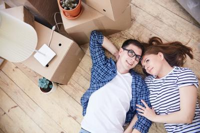 Young couple lying on floor next to moving boxes