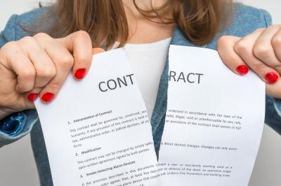 Close up of woman ripping a contract in two