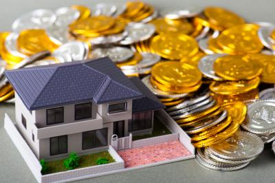 Miniature house with large coins representing house flipping