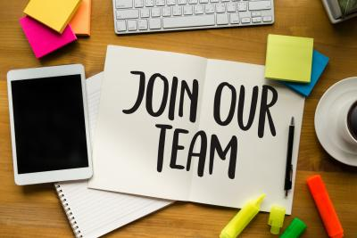 Sign saying 'join our team' on desk beside keyboard and post it notes