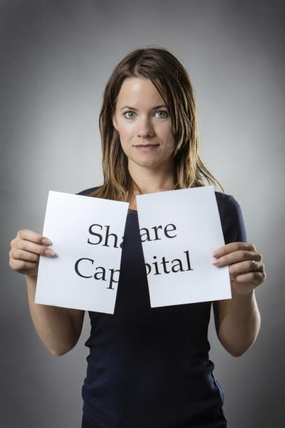 Woman holding ripped sign saying share capital
