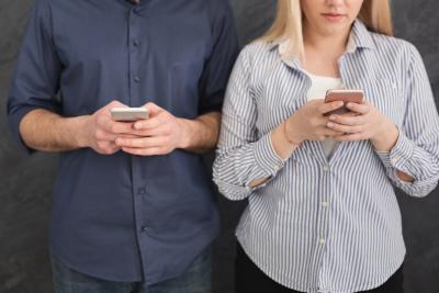 Man and woman standing side by side staring at their phone screens